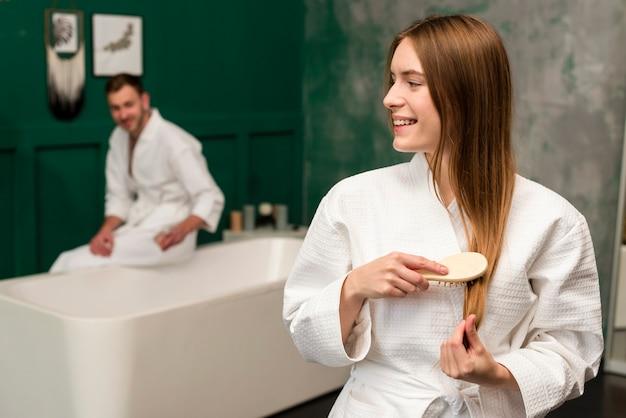 Vue latérale d'une femme en peignoir se brosser les cheveux