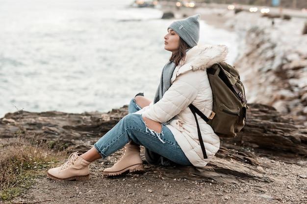 Vue latérale de la femme à la plage seule