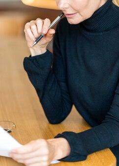 Vue latérale d'une femme plus âgée au travail, lire des papiers