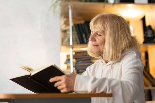 Vue latérale d'une femme plus âgée lisant un livre à la maison