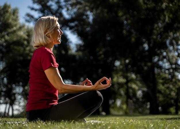 Vue latérale d'une femme plus âgée en position du lotus à l'extérieur pendant le yoga