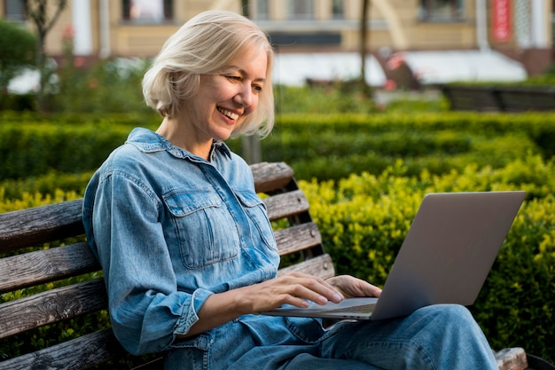Vue latérale d'une femme plus âgée smiley à l'extérieur sur un banc avec un ordinateur portable