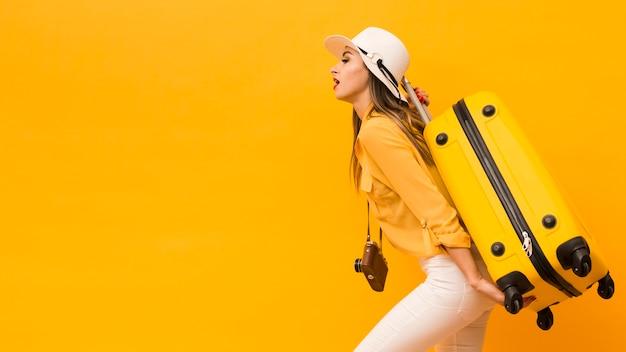 Vue latérale d'une femme portant des bagages et un appareil photo