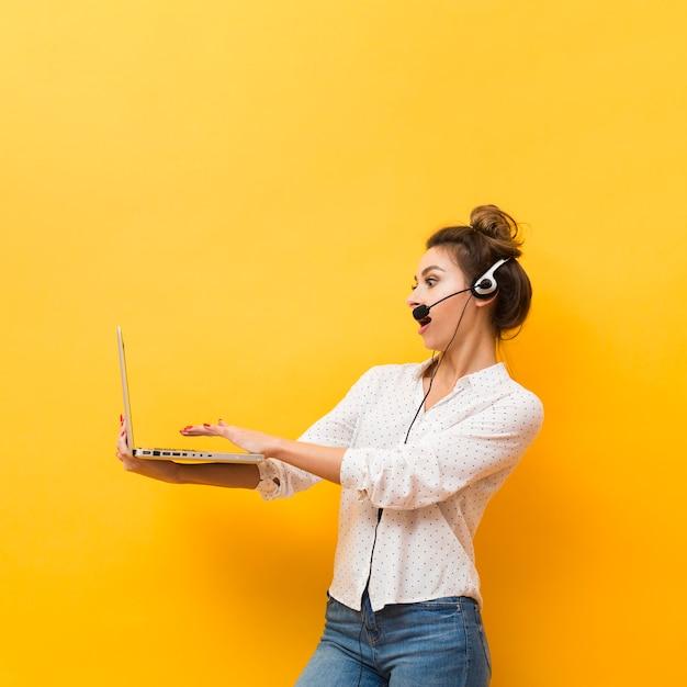 Vue latérale d'une femme portant un casque et tenant un ordinateur portable