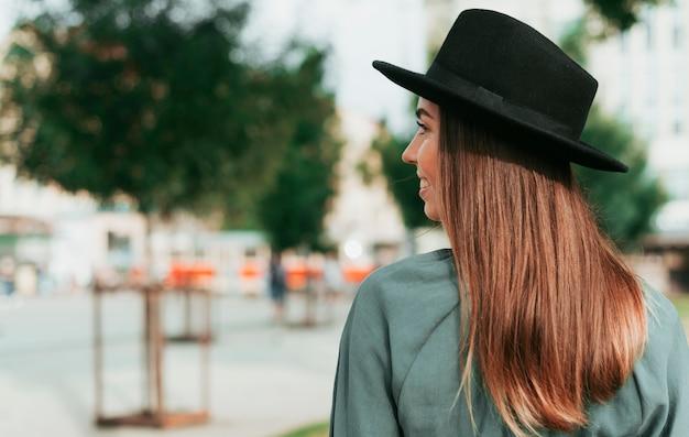 Vue latérale femme portant un chapeau noir avec espace copie