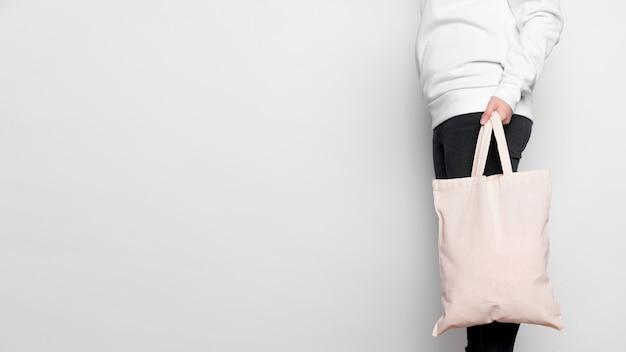 Vue latérale femme portant sac fourre-tout en tissu