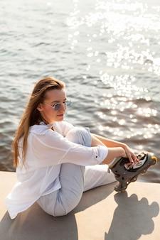 Vue latérale d'une femme posant au bord du lac avec des patins à roulettes