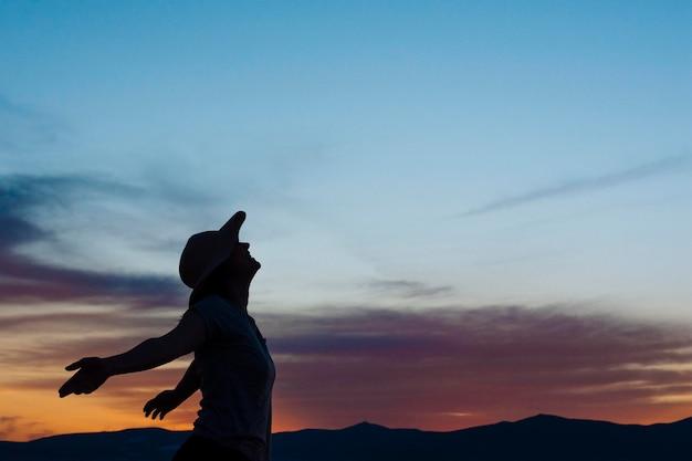 Vue latérale d'une femme posant au coucher du soleil dans la nature