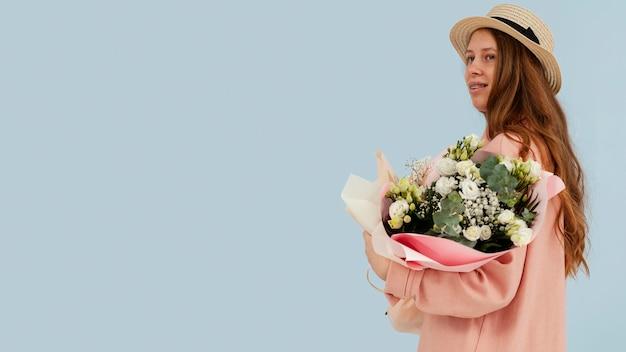 Vue latérale de la femme posant avec bouquet de fleurs de printemps et espace copie