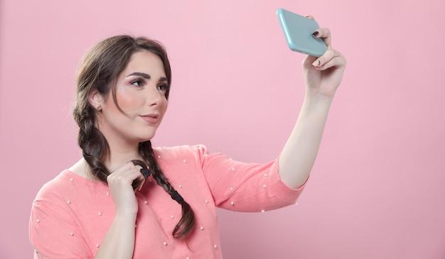 Vue latérale d'une femme posant pour un selfie tout en tenant un smartphone