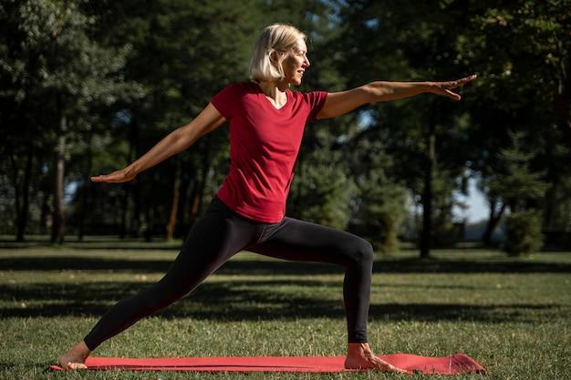 Vue latérale, de, femme, pratiquer, yoga, position, dehors