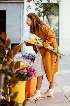 Vue latérale d'une femme qui achète des fleurs de printemps à l'extérieur