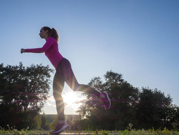 Vue latérale d'une femme qui court dans la zone du parc de la ville pendant le coucher du soleil.