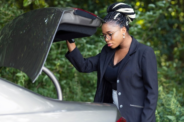 Vue latérale d'une femme regardant à travers le coffre de sa voiture