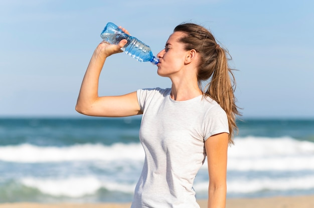 Vue latérale d'une femme restant hydratée pendant l'entraînement à la plage