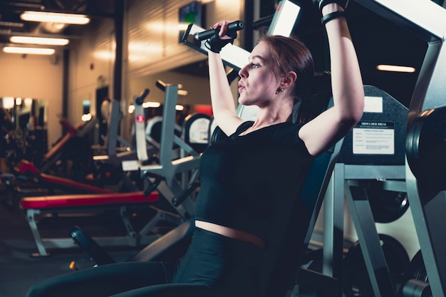 Vue latérale d'une femme s'exerçant sur la machine de presse d'épaule