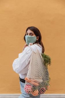 Vue latérale d'une femme avec des sacs d'épicerie à l'extérieur