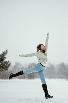 Vue latérale d'une femme sautant en l'air à l'extérieur en hiver