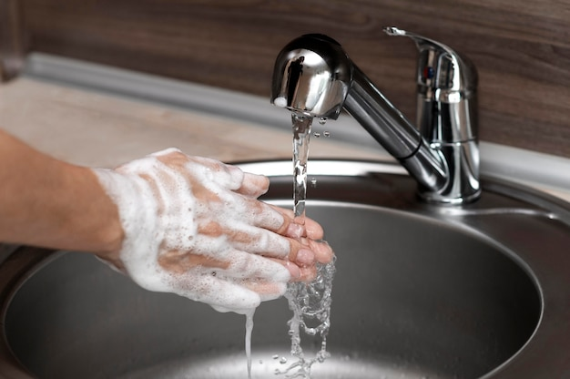 Vue latérale femme se laver les mains dans un évier