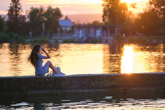 Vue latérale d'une femme seule assise seule au bord du lac par une chaude soirée. solitude et détente dans le concept de la nature.