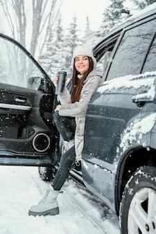 Vue latérale d'une femme souriante appréciant la neige lors d'un voyage sur la route et prenant une boisson chaude