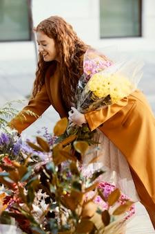Vue latérale d'une femme souriante en choisissant le bouquet de fleurs de printemps
