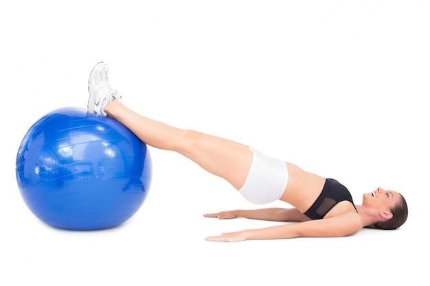 Vue latérale d'une femme souriante en forme de mentir avec ballon d'exercice