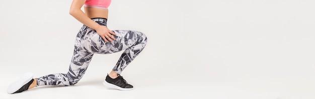 Vue latérale d'une femme sportive faisant des fentes