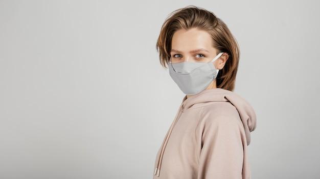 Vue latérale femme en sweat à capuche avec masque