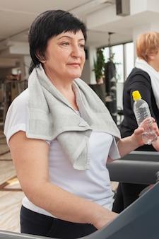 Vue latérale femme sur tapis roulant