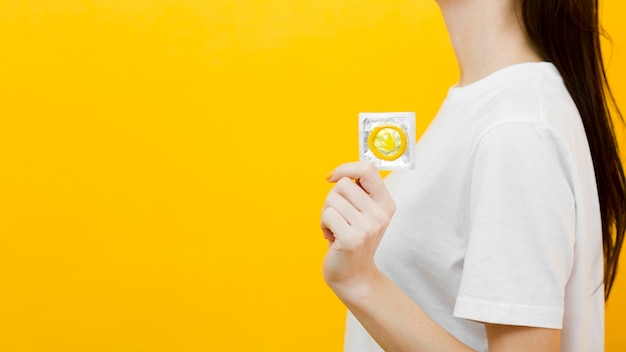 Vue latérale femme tenant un préservatif avec copie espace