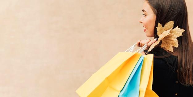 Vue latérale femme tenant des sacs à provisions avec espace copie