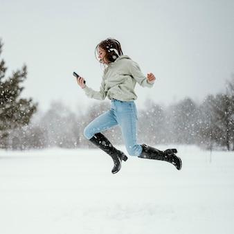 Vue latérale d'une femme tenant un smartphone et sautant en l'air à l'extérieur tout en utilisant des écouteurs