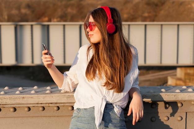 Vue latérale d'une femme tenant un smartphone tout en portant des lunettes de soleil et des écouteurs