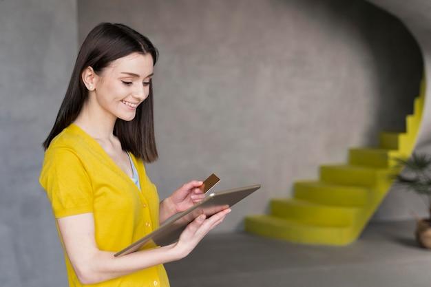 Vue latérale d'une femme tenant une tablette et une carte de crédit