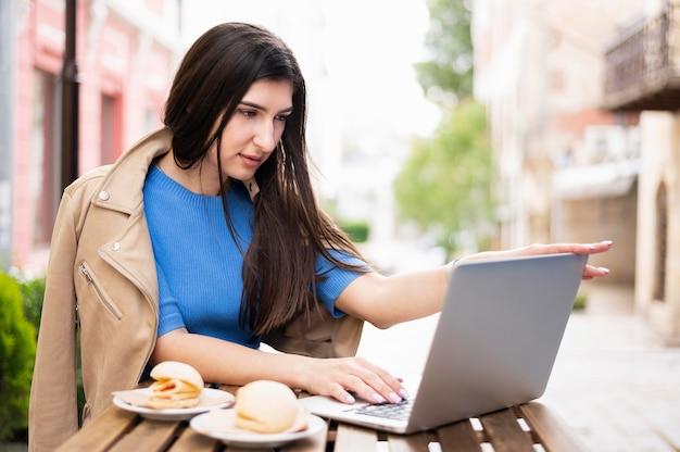 Vue latérale d'une femme travaillant à l'extérieur tout en déjeunant