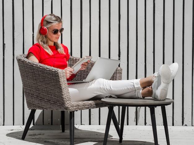 Vue latérale d'une femme travaillant sur un ordinateur portable à l'extérieur tout en portant des écouteurs