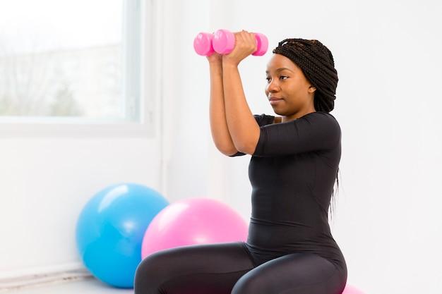 Vue latérale femme travaillant avec des poids