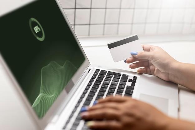 Vue latérale d'une femme utilisant un ordinateur portable pour faire des achats en ligne avec une carte de crédit