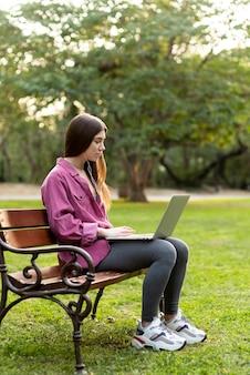 Vue latérale femme vérifiant son ordinateur portable sur un banc