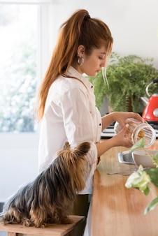Vue latérale femme wit chien à côté dans la cuisine