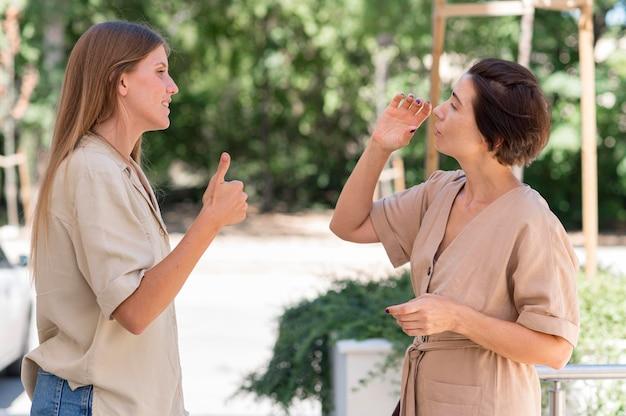 Vue latérale des femmes à l'extérieur conversant par la langue des signes