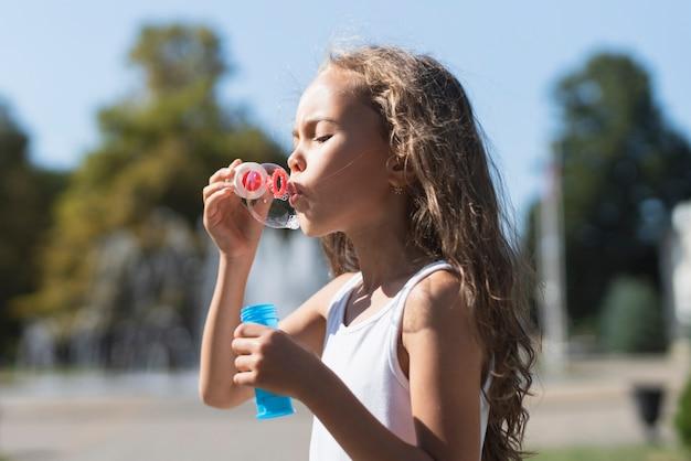 Vue latérale d'une fille jouant avec des bulles de savon