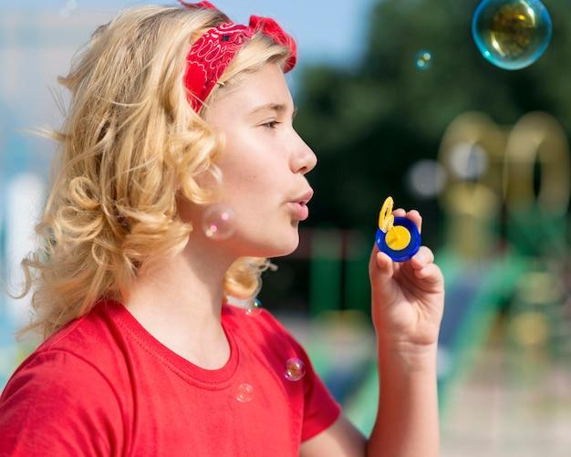 Vue latérale fille jouant avec souffleur de bulles