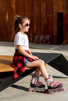 Vue latérale d'une fille avec des patins à roues alignées