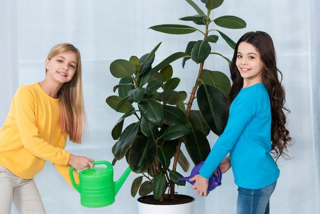 Vue latérale filles arrosant des fleurs