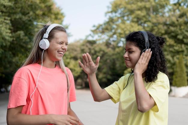 Vue latérale des filles écoutant de la musique
