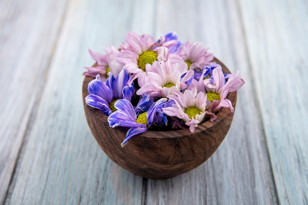 Vue latérale des fleurs dans un bol sur fond de bois