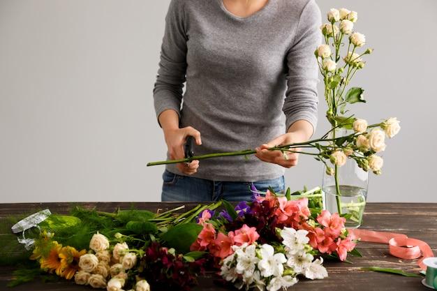 Vue latérale des fleurs, fleuriste coupant la tige.
