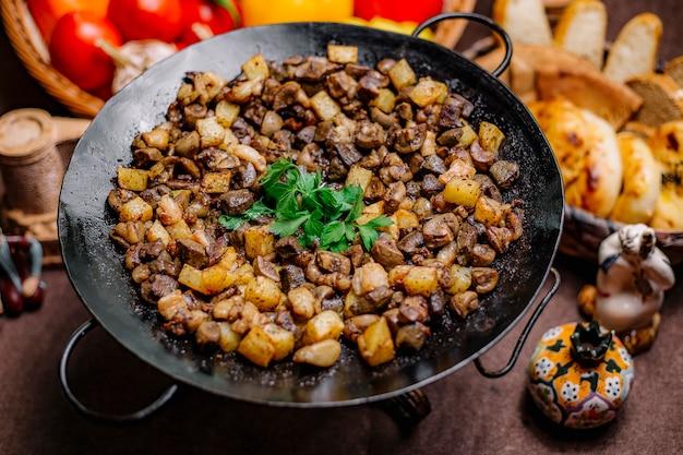 Vue latérale foie d'agneau grillé avec pomme de terre et légumes verts